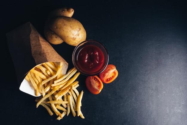 Вид сверху картофеля фри с кетчупом и сырым картофелем на черном фоне. пространство для копирования