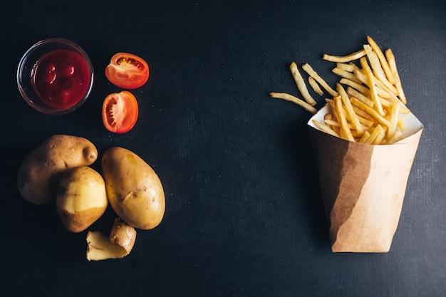 Вид сверху картофель-фри с кетчупом и сырым картофелем на черном фоне.