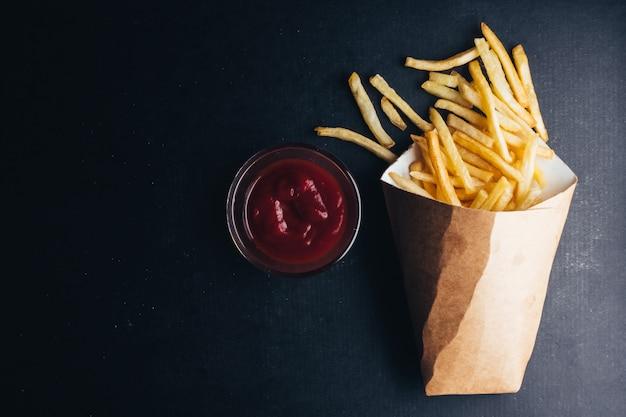 Вид сверху картофель-фри с кетчупом на черном фоне. пространство для копирования