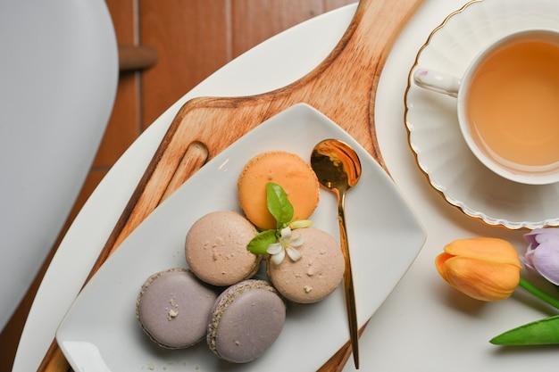 木製トレイの上のフランスのマカロンとリビングルームのコーヒーテーブルの上のティーカップの上面図
