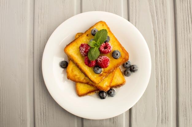 Вид сверху французских тостов с ягодами и медом