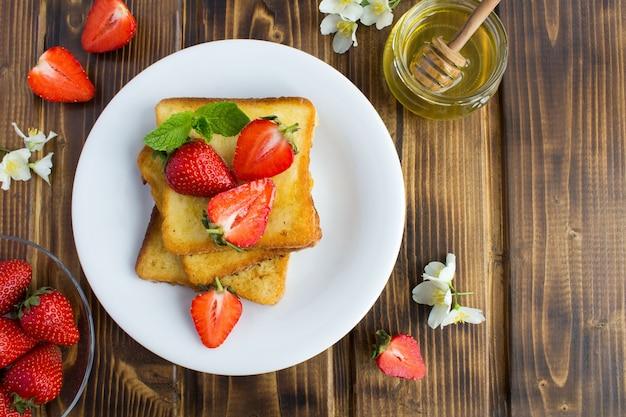 木製のテーブルにイチゴと蜂蜜とフレンチトーストのトップビュー