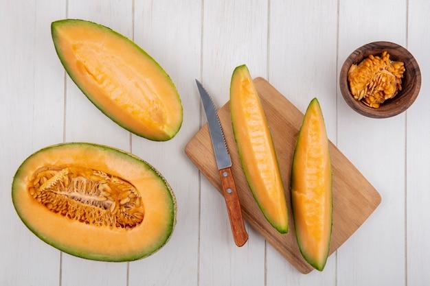 Вид сверху свежих и вкусных ломтиков дыни на деревянной кухонной доске с ножом с семенами на деревянной миске на белом дереве