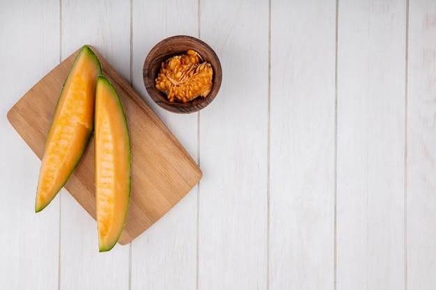 Вид сверху свежей и вкусной дыни с семенами на деревянной миске на белом с копией пространства