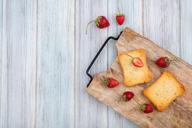Вид сверху свежей и вкусной клубники с поджаренными кусочками хлеба на деревянной кухонной доске на сером деревянном фоне с копией пространства