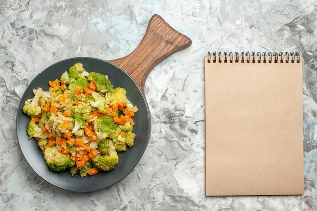 木製のまな板と白いテーブルの上のノートに新鮮で健康的な野菜サラダの上面図