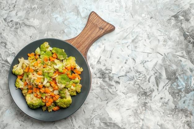 白いテーブルの上の木製まな板に新鮮で健康的な野菜サラダの上面図