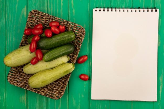 コピースペースのある緑の木製の壁の枝編み細工品トレイに梅トマトきゅうりとズッキーニなどの新鮮で健康的な野菜の上面図