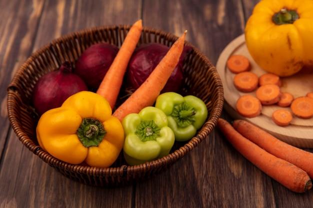 木製の表面のバケツに赤玉ねぎ、カラフルなピーマンとニンジンなどの新鮮で健康的な野菜の上面図