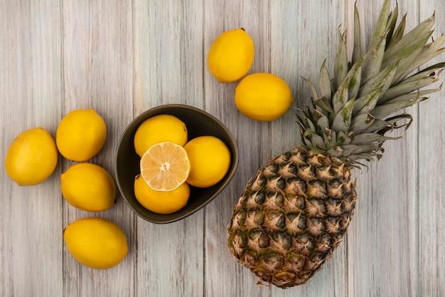 Вид сверху свежих и сочных лимонов на миске с ананасом и лимонами, изолированными на серой деревянной поверхности