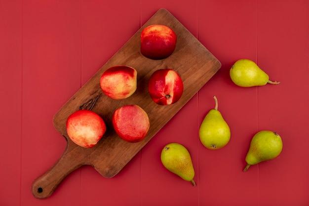 Вид сверху свежих и сочных персиков на деревянной кухонной доске с грушами на красном фоне