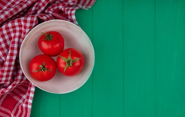 コピースペースと緑の木製の背景の上の赤いチェックの布のボウルに新鮮な赤いトマトの上面図