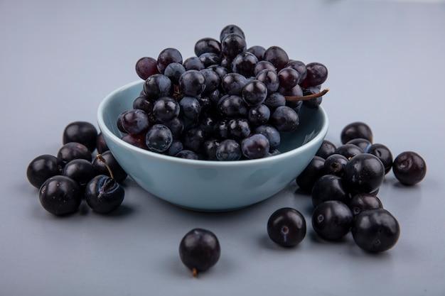 회색 배경에 파란색 그릇에 신선하고 달콤한 맛 검은 포도의 상위 뷰