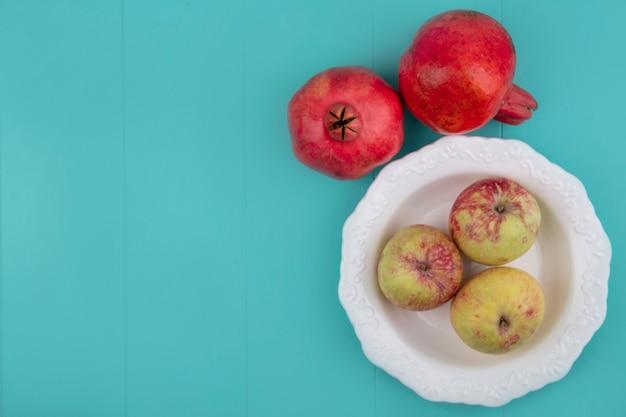コピースペースと青い背景に分離されたザクロとボウルに新鮮なリンゴの上面図
