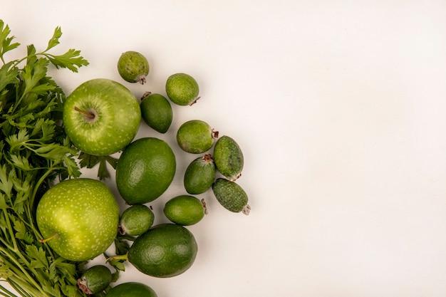 Вид сверху свежих яблок с лаймами фейхоа и петрушкой, изолированных на белой стене с копией пространства