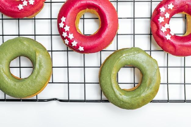 冷却ラックに鮮やかなピンクとグリーンのアイシング、スター振りかけると焼きたてのドーナツのトップビュー