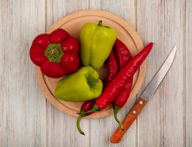 Вид сверху свежего болгарского перца и перца чили на деревянной кухонной доске с ножом на серой деревянной стене