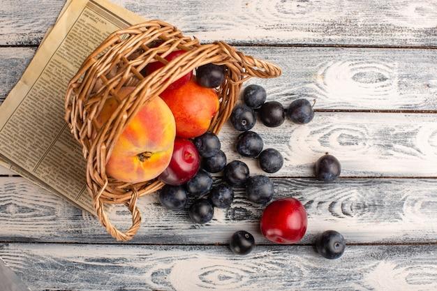 灰色の木製の表面に桃とバスケットの中の新鮮なブラックソーンのトップビュー