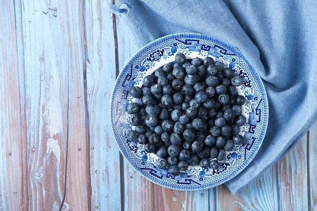 Вид сверху свежей голубой ягоды на тарелке на столе