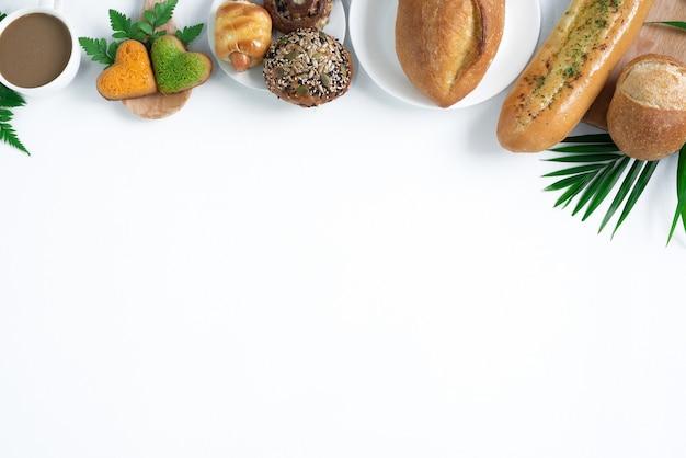 흰색 배경 나무에 분리된 신선한 빵과 커피펀 리프몬스테라 잎의 상위 뷰