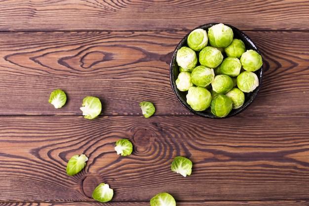 나무 테이블에 신선한 브뤼셀 콩나물의 최고 볼 수 있습니다. 텍스트를 놓습니다. 평평하다.