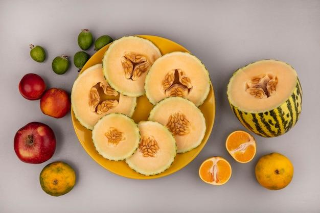 Вид сверху кусочков свежей дыни на желтой тарелке с яблоками, мандаринами и фейхоа, изолированными на белой стене