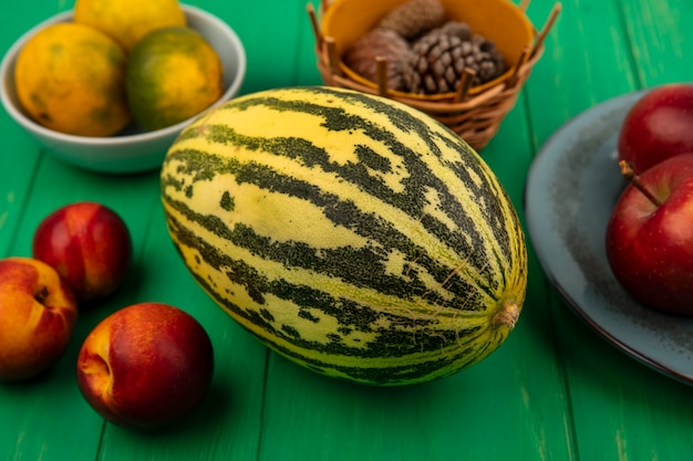Вид сверху свежей дыни с красными яблоками на тарелке с мандаринами на миске с персиками, изолированными на зеленой деревянной стене
