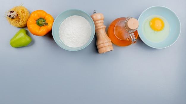 コピースペースと白い背景の上の新鮮な鶏の卵白とリンゴ酢と小麦粉のピーマンと卵黄の平面図