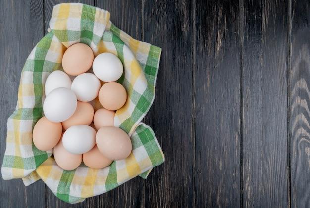 Вид сверху свежих куриных яиц на проверенной скатерти на деревянном фоне с копией пространства