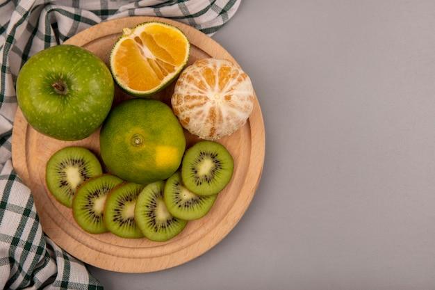 Вид сверху свежих нарезанных ломтиков киви на деревянной кухонной доске на клетчатой ткани с зеленым яблоком и мандарином с копией пространства