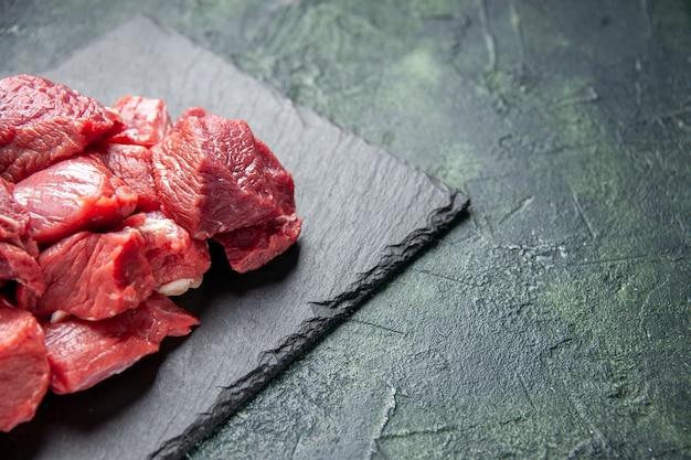 緑と黒の混合色の背景の右側にある黒い板に新鮮なみじん切りの生の牛肉ステーキの上面図