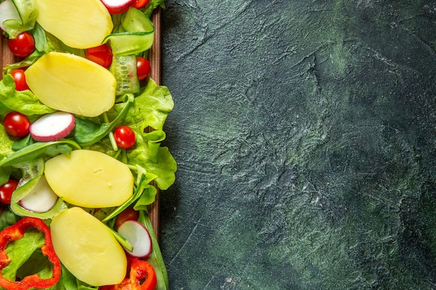 Вид сверху свежих нарезанных овощей на деревянном подносе с правой стороны на фоне смешанных цветов со свободным пространством