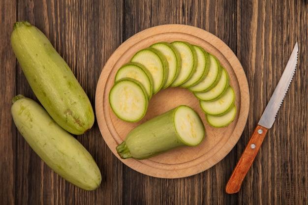 木製の表面に分離されたズッキーニとナイフで木製のキッチンボード上の新鮮な刻んだズッキーニの上面図 無料写真