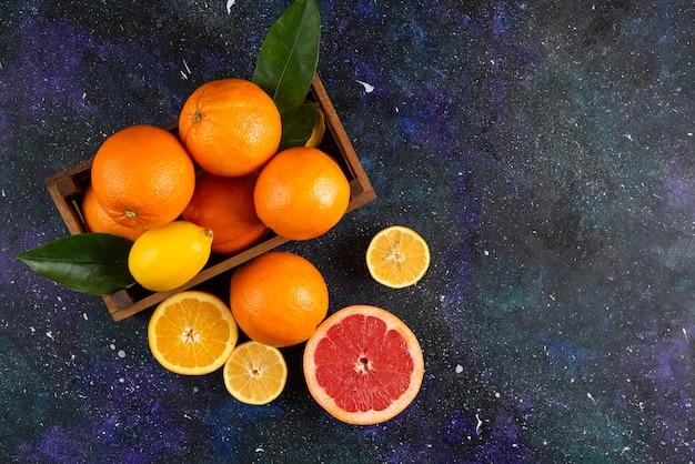 木製のバスケットまたは地面に新鮮な柑橘系の果物の上面図。 。