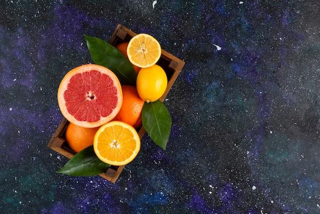 木製のバスケットに新鮮な柑橘系の果物の上面図。