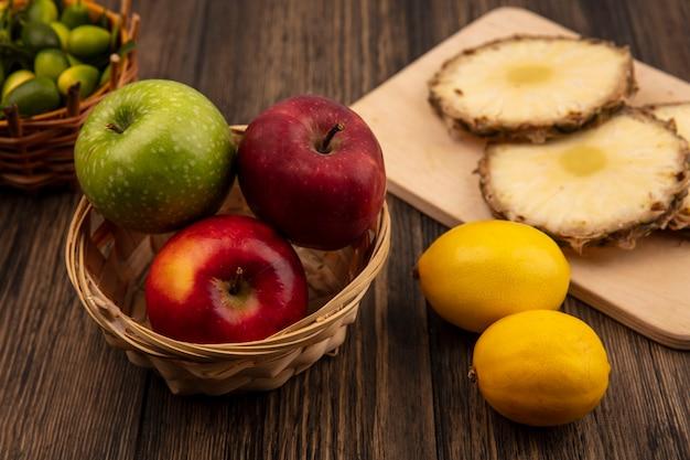 木製の壁に隔離されたレモンとバケツにキンカンと木製のキッチンボードにパイナップルとバケツに新鮮なカラフルなリンゴの上面図