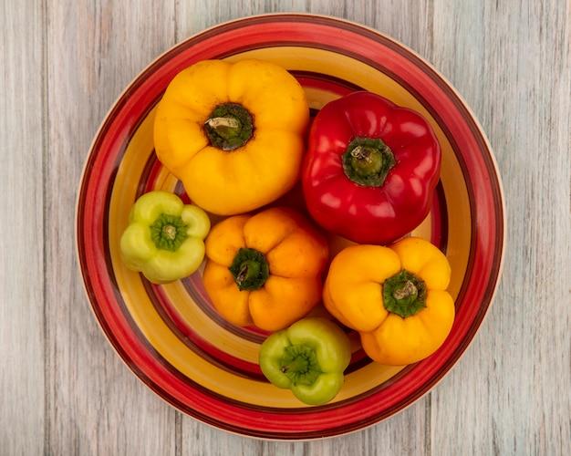 Вид сверху свежих красочных болгарских перцев на тарелке на серой деревянной поверхности