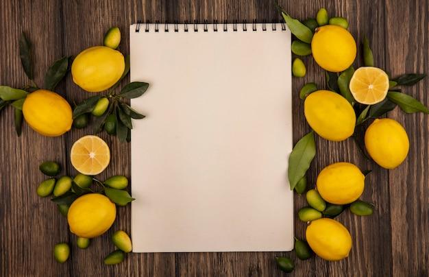 Вид сверху на свежие красочные фрукты, такие как лимоны и кинканы, изолированные на деревянной поверхности с копией пространства