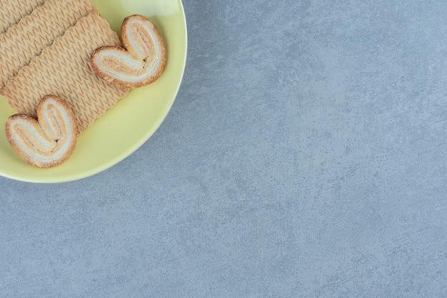 新鮮なクッキーの上面図。黄色いプレートに美味しいおやつ。