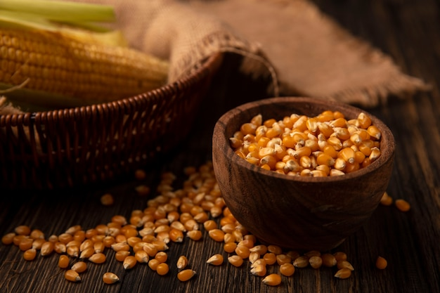 Вид сверху свежих зерен кукурузы на деревянной миске с зернами, изолированными на деревянной стене