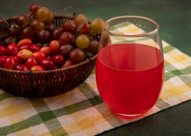 緑の表面のガラスに新鮮なジュースとブドウとチェックされた布のバケツに新鮮なコーネリアンチェリーの上面図