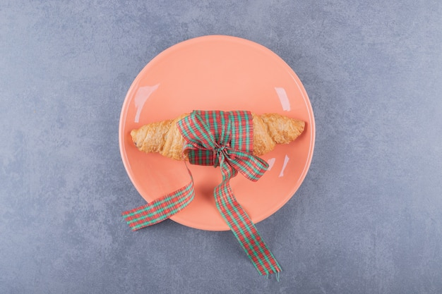Вид сверху свежего круассана на оранжевой тарелке.