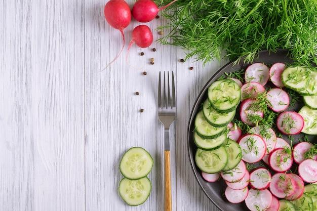 新鮮なキュウリと大根のディルと植物油のサラダの上面図。ベジタリアンダイエット。減量のためのディエスタ。健康的な食事。セレクティブフォーカス。スペースをコピーします。