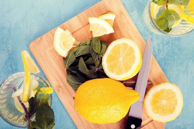 青いヴィンテージの木の板にレモネードと2つのグラスの横にある新鮮なカットレモンの上面図