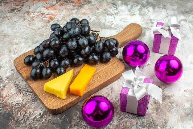 나무 커팅 보드에 있는 신선하고 맛있는 검은 포도 다발과 치즈, 혼합 색상 배경에 있는 선물 장식 액세서리의 상위 뷰