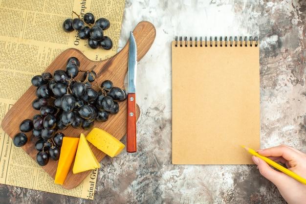 混合色の背景のノートブックの横にある木製のまな板とナイフの新鮮なおいしい黒ブドウの束とさまざまな種類のチーズの上面図