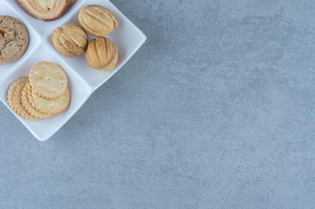 白いプレート上の新鮮なおいしいクッキーの上面図。