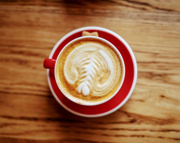 カフェテリアの机の上のクリームと新鮮なおいしい一杯のコーヒーのトップビュー