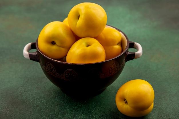 Вид сверху свежих вкусных персиков на миске на зеленом фоне