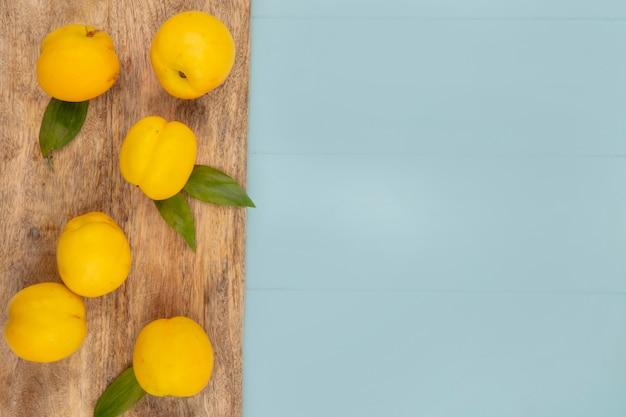 Вид сверху на свежие вкусные желтые персики, изолированные на деревянной кухонной доске на синем фоне с копией пространства